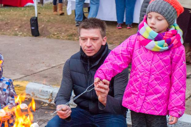 Natalia Czajaa (5) and her dad Jack make smores in the fire pit during the welcoming of the U.S. Capitol Christmas tree event in Centennial Park.
