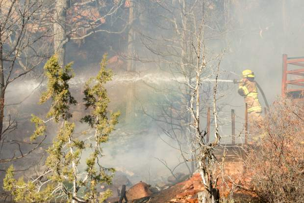 Firefighters work to control a fire that destroyed one house and damaged two others near Thunder River Market off Colorado Highway 82.