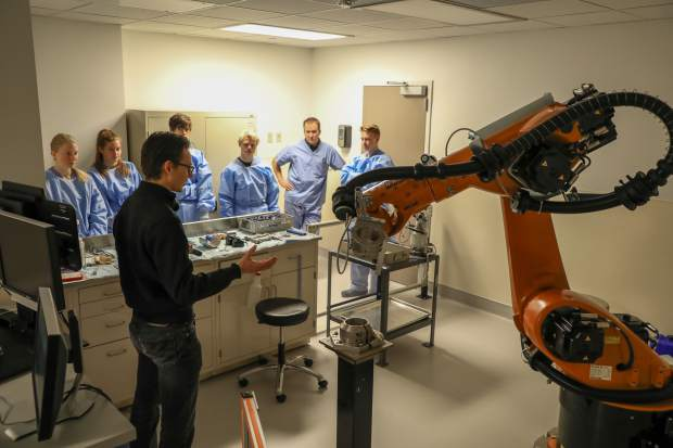 Robotics engineer Alex Brady, with the Steadman Philippon Research Institute, expalins to students from Vail Ski & Snowboard Academy how robots help inovate surgery techniques on Tuesday at the Vail Valley Medical Center in Vail. The robot is an old car manufacuring robot programed to help with new inovations in orthopedic surgery.
