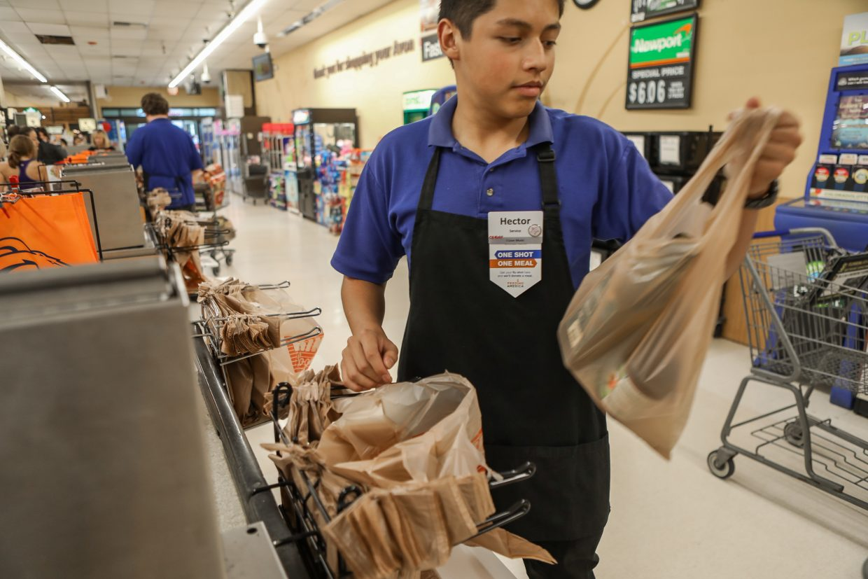 Hector Palacios places plastic bags into a shopping cart at checkout at the City Market in Avon.