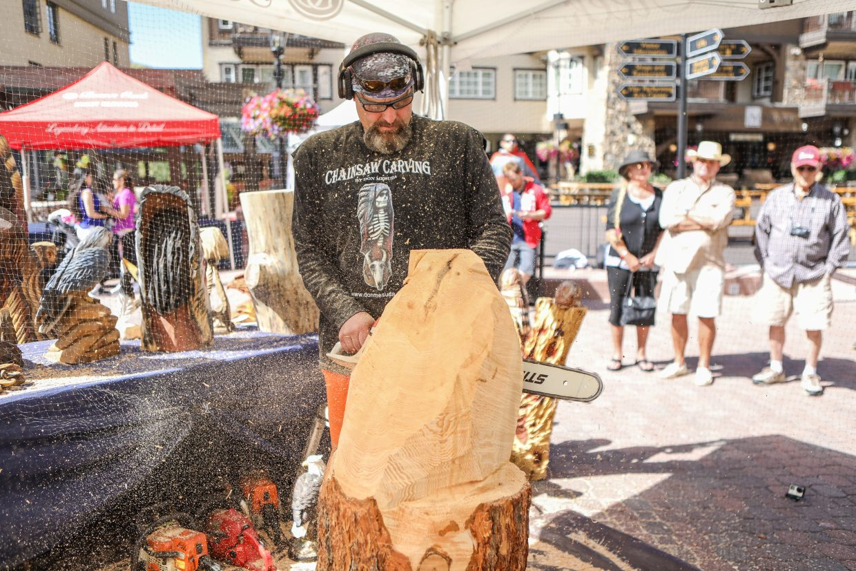 Don Mesuda carves into a chunk of wood with a chainsaw as it begins to take flight as an eagle for Beaver Creek's Hike to the Mic weekend event Friday, Sept. 15, in Beaver Creek. Mesuda has been carving wood with chainsaws for only a few years.