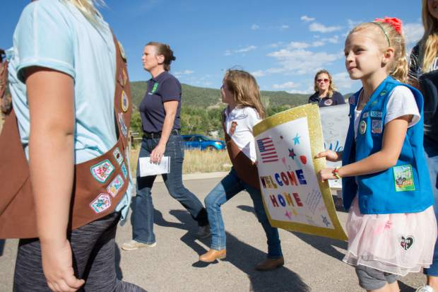 The local Girl Scout troop helps lead the parade before the Building Homes for Heroes ceremony and house reveal.