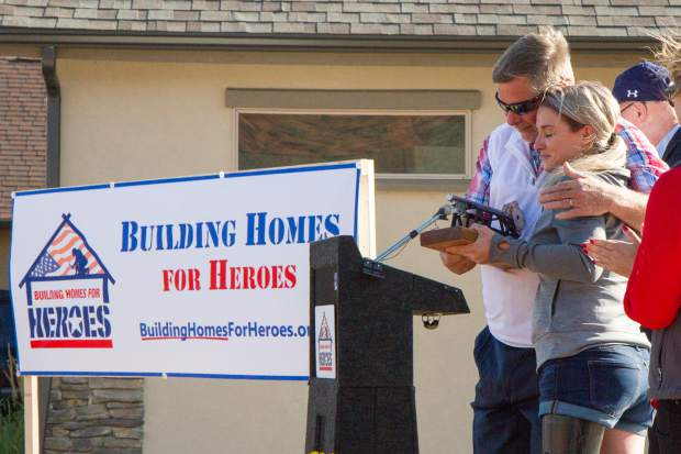 Veteran Sgt. Kirstie Ennis is awarded the key to Ironbridge during the Building Homes for Heroes ceremony and house reveal on Saturday evening.