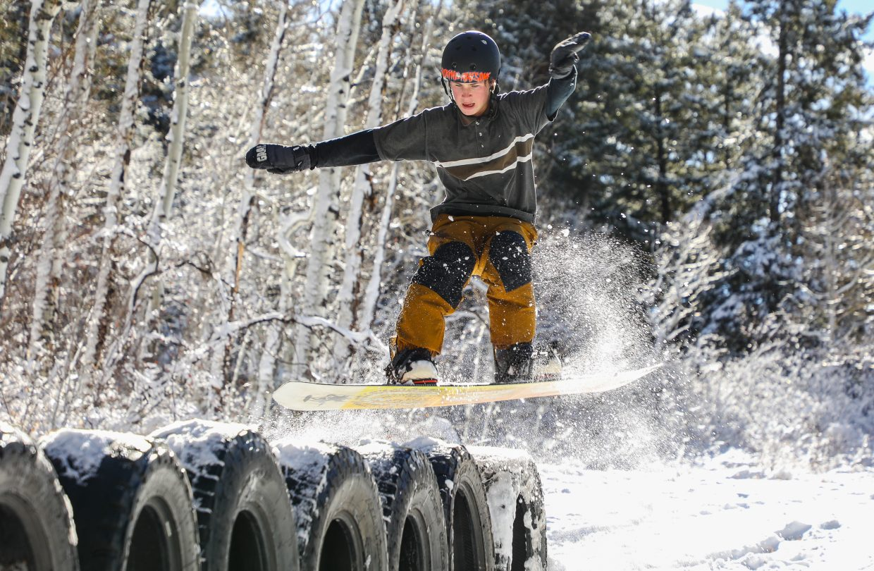 Dylan Okurowski goes for a 180 degree rotation into a 50/50 grind on a series of tires in the new snow Sunday, Nov. 19, at Maloit Park in Minturn. Okurowski said he had been out enjoying the new snow throughout the weekend.