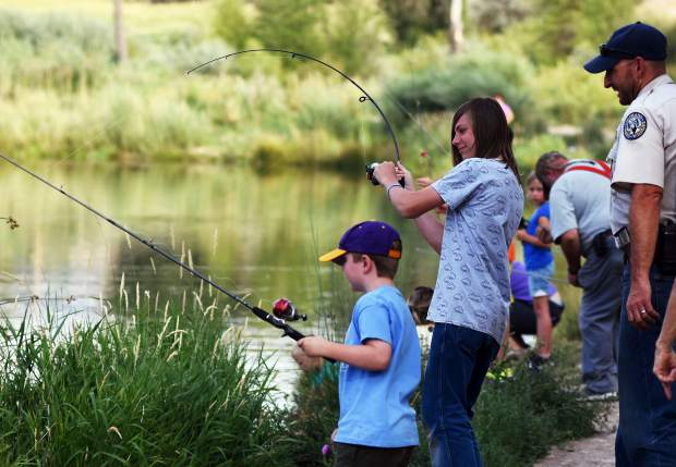 Gypsum Daze fishing2 KA 7-21-18 Kristin Anderson Levi Metzger, center, reels in his first catch, a Rainbow Trout, as District Wildlife Manager, Brian Wodrich, right, looks on during the Gypsum Daze Fishing is Fun event Thursday at Gypsum Ponds.