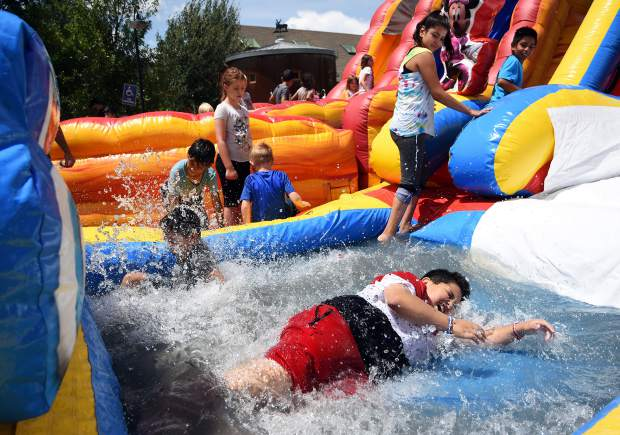 Gypsum Daze slide KA 7-21-18 Kristin Anderson Pedro Cervantes, 10, pushes through water at the end of an inflatable slide during Gypsum Daze on Satuday in Gypsum.