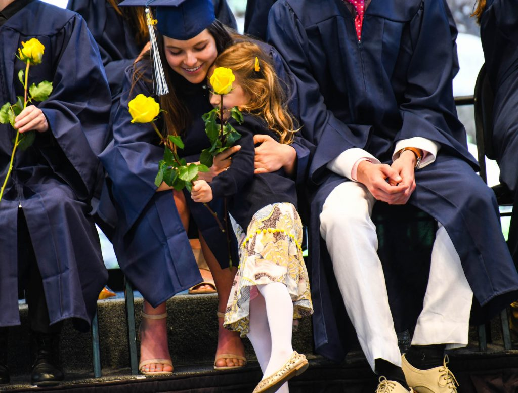 A kindergartner presents a VMS senior with a yellow rose on Friday at commencement.