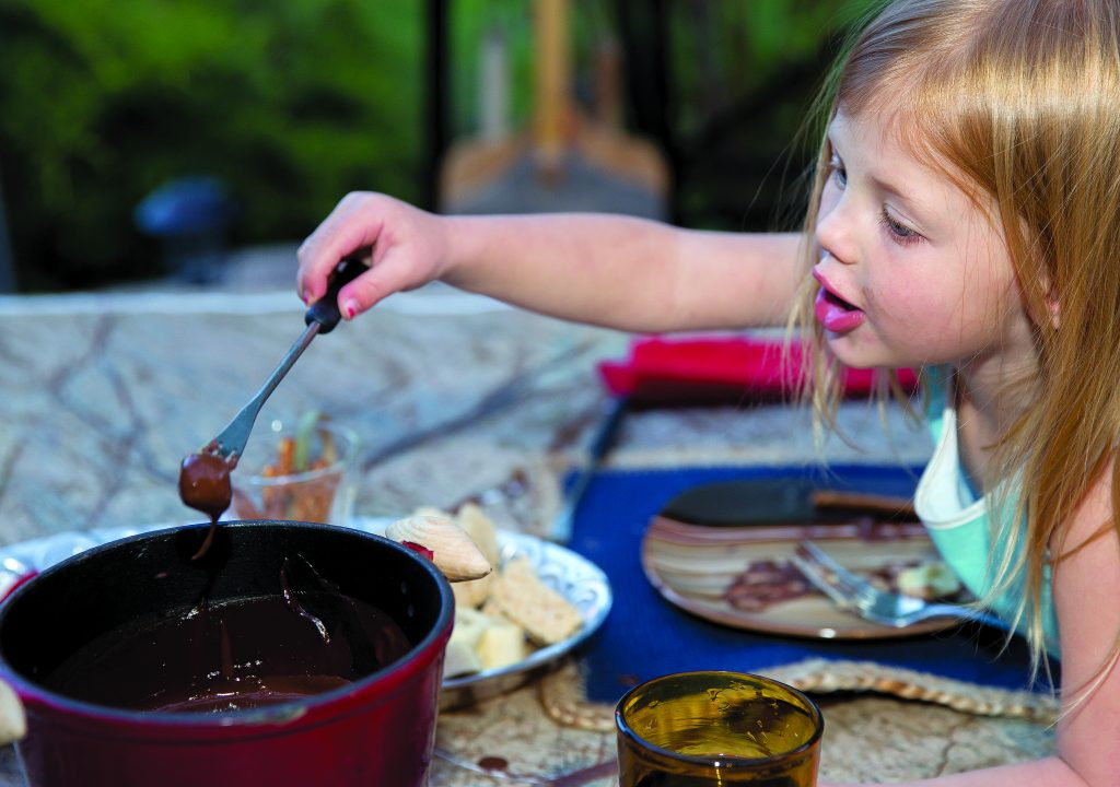 Valen Larese, 3, dips her marshmellow in a pot of melted Belgium chocolate provided by Fondue at Home.