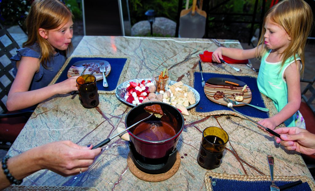 Zoe Larese, 11, and Valen Larese, 3, enjoy the Fondue at Home dessert which includes a pot of melted Belgium chocolate along with a selection of sweet treat to dip in the pot, like fresh strawberries, rice crispy treats and marshmellows.