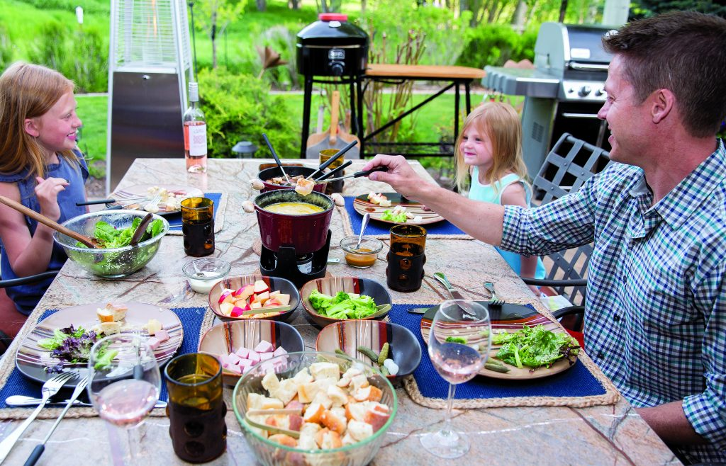 Fondue at Home provides the perfect summer outdoor dining experience a fully catered fondue meal at home. The meal includes a melted cheese pot and a hot pot of beef broth that stays warm as the evening cools down along with plenty of meat, bread and vegetable options to dip in the fondue and a fresh salad and a dessert fondue pot.