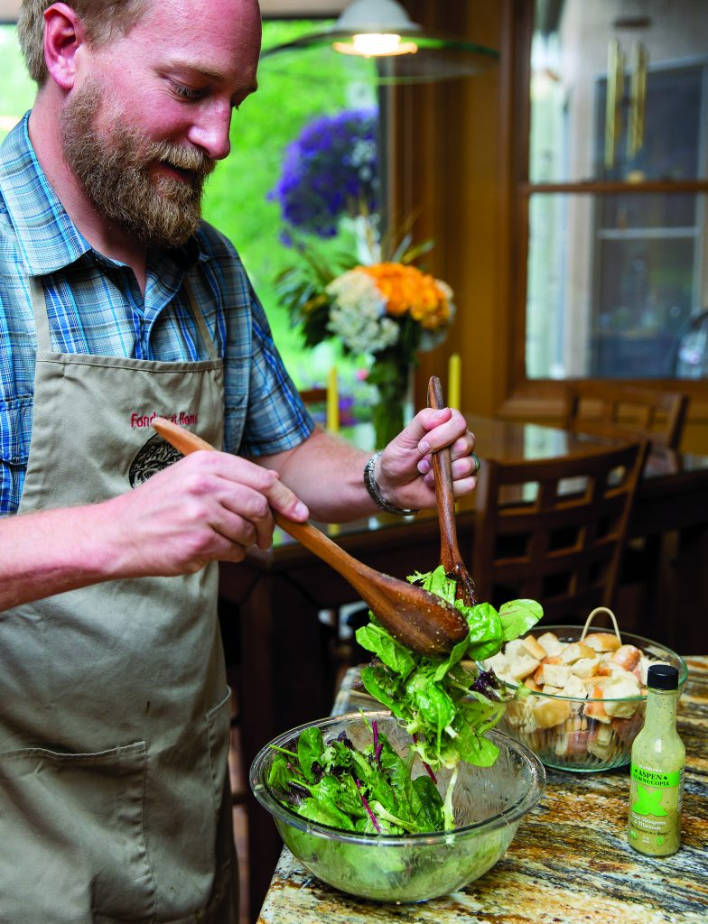 Derek George, owner of Fondue at Home, tosses salad as part of the Fondue at Home experience.