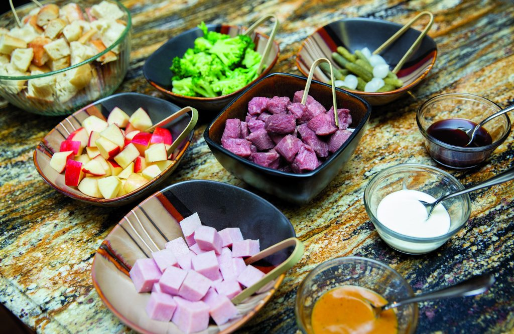 A selection of meat, bread abd vegetables as well as sauces  that make up the Fondue at Home dining experience.