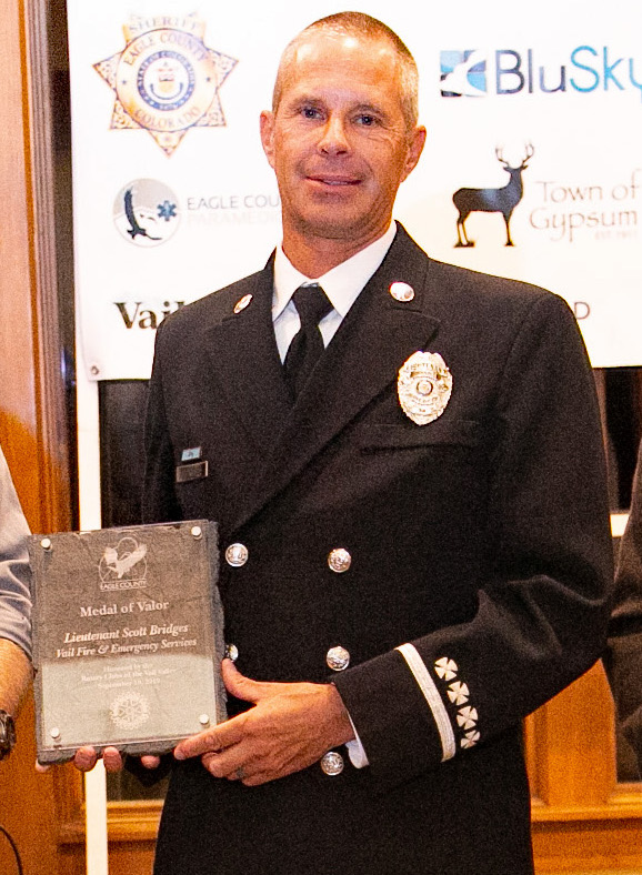 Medal of Valor Lt. Scott Bridges, Vail Fire and Emergency Services  Bridges has been with Vail Fire and Emergency Services since 1999.  At 6 a.m., March 1, 2019, Bridges was on his way to Vail Fire to begin his shift. The upper Vail Valley was being hammered by a snowstorm and the roads were slick and icy.  Multiple vehicles collided on eastbound I-70 in Eagle-Vail. Lt. Bridges was driving by and was on the scene before on-duty first responders. As he slowly drove past the scene, he rolled down his passenger window to ask if there were any injuries. That's when heard someone crying for help. He parked his car just beyond the scene and jumped out to help.  That's when another vehicle lost control and struck several of the vehicles involved in the original accident. That collision drove one of the already-wrecked vehicles into Bridges. He was thrown quite a distance, suffered a head injury, facial injuries, and orthopedic injuries. He spent several days in intensive care and has undergone several surgeries. He's still recovering, and won't be able to return to full duty for approximately 11 months.