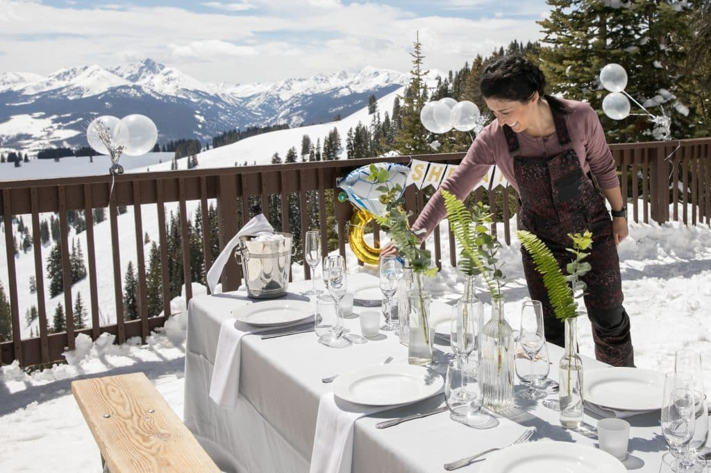 Stephanie Fleck, owner of Party Girl Events puts the finishing touches on Mariana and Fernando's engagement at Window's Deck in Vail. All the china, linens, glassware, florals, balloons and food catered by Spendido were brought up Gondola One and a chair lift for a mountain top picnic proposal.